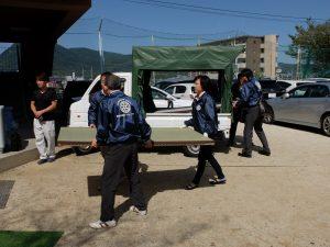 畳を運ぶ小山新会員、森崎会員、下川会員